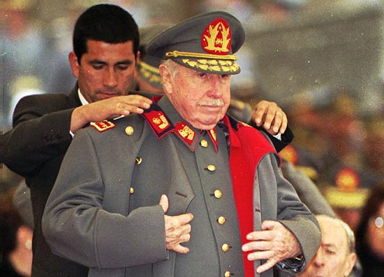 ORG XMIT: XLAT128 FILE - In this Aug. 23, 1995 file photo, former Chilean dictator and military commander Gen. Augusto Pinochet is helped by a bodyguard to put on his coat during a military ceremony in Santiago, Chile, on the occasion of the 22nd anniversary of his taking the post as head of the Chilean armed forces. Months after his appointment in 1973, Pinochet led the coup that ousted President Salvador Allende. Pinochet sympathizers will honor the former strongman on Sunday, June 10, 2012 with the screening of a new documentary about his dictatorship years in a Santiago theater. (AP Photo/Santiago Llanquin, File)
