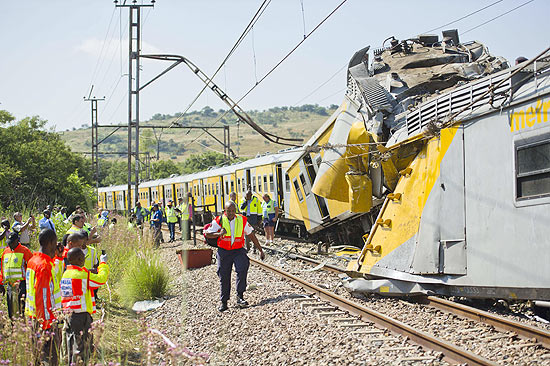 ORG XMIT: RSA001 Rescuers work on the site of a train accident near Kalefong station, Attridgeville, in the west of Pretoria on January 31, 2013. The collision between two passenger trains packed with school kids and rush-hour commuters in Pretoria that injured up to 300 people has being blamed on cable theft, the authorities said. The crash took place at around 7.10am (0510 GMT) when a commuter train heading from the suburbs to the capital ploughed into a stationary train on the same track. AFP PHOTO / STRINGER