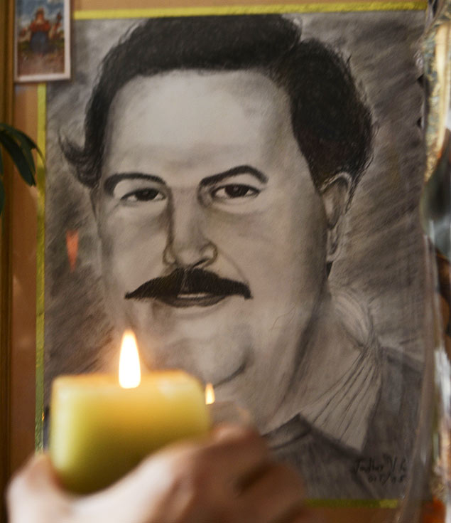 TO GO WITH AFP STORY BY ARIELA NAVARRO Wberney Zabala, a resident of the Pablo Escobar neighborhood, lights a candle as he prays before the portrait of Colombian drug lord Pablo Escobar, on November 24, 2013 in Medellin, Antioquia department, Colombia. The Napoles ranch, built on an area of 2,200 hectares by late drug lord Pablo Escobar, has turned into a theme park with a memorial museum, exotic animals and a simulation of a jurassic park. December 2, 2013 marks the 20th anniversary of Escobar's death. AFP PHOTO/Raul ARBOLEDA ORG XMIT: RAM009
