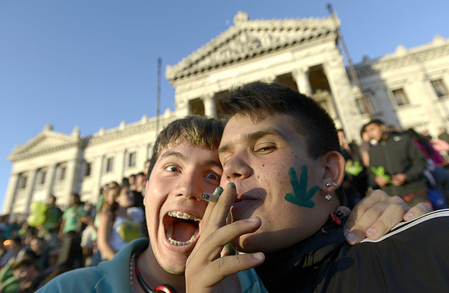 An activist smokes a marijuana cigarette as they poses for photos in front of the Congress in Montevideo, Uruguay, Tuesday, Dec. 10, 2013. Uruguay's Senate approved the world's first national marketplace for legal marijuana Tuesday, an experiment that puts the government in charge of growing, selling and using a drug that is illegal almost everywhere else. (AP Photo/Matilde Campodonico) ORG XMIT: MVD120