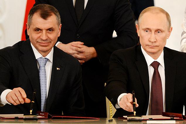 Presidente russo, Vladimir Putin (dir.), e o presidente do Parlamento da Crimeia, Vladimir Konstantionov, assinam tratado de anexação da península à Rússia