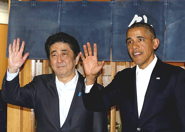 U.S. President Barack Obama (R) waves next to Japan's Prime Minister Shinzo Abe after dinner at Sukiyabashi Jiro restaurant in Tokyo, April 23, 2014. Obama arrived in Tokyo on Wednesday at the start of a four-nation trip that comes at a time of rising tension in the region, and as the United States urges Japan's unpredictable neighbour North Korea not to conduct another nuclear test. REUTERS/Larry Downing (JAPAN - Tags: POLITICS TPX IMAGES OF THE DAY) ORG XMIT: WAS307