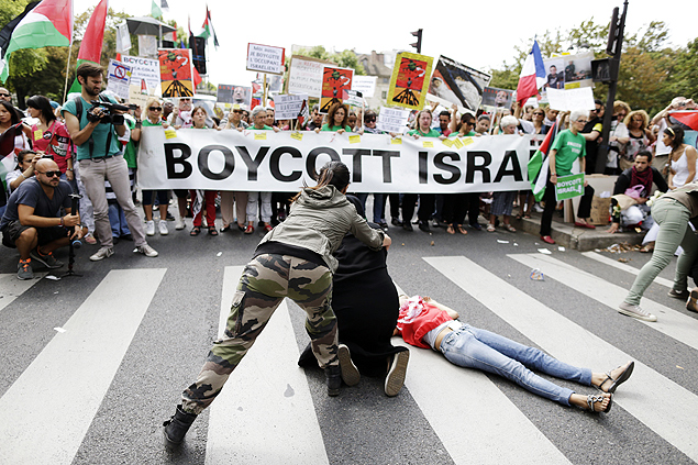 "People stage a scene as demonstraters hold a banner reading ""Boycott Israel"" during a demonstration against Israel's military operations in Gaza and in support of the Palestinian people, on August 2, 2014 in Paris. The Israeli army on on August 2 informed residents of Beit Lahiya in northern Gaza that it was ""safe"" to return to their homes, as witnesses said troops were seen withdrawing from the area. AFP PHOTO / KENZO TRIBOUILLARD ORG XMIT: -"
