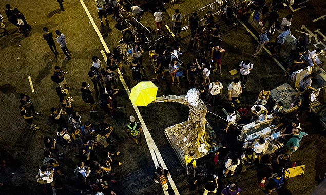 """The statue """"Umbrella Man"""" by the Hong Kong artist known as Milk, is set up at a pro-democracy protest site next to the central government offices in Hong Kong on October 5, 2014. Pro-democracy demonstrators stood divided Sunday over whether to withdraw from protest sites across Hong Kong, hours before a government deadline to clear key roads they have blockaded for the last week. Embattled Chief Executive Leung Chun-ying has said his administration was determined to """"take all necessary actions to restore social order"""" and pave the way for government staff to resume work by Monday morning. AFP PHOTO / XAUME OLLEROS RESTRICTED TO EDITORIAL USE, MANDATORY CREDIT OF THE ARTIST, TO ILLUSTRATE THE EVENT AS SPECIFIED IN THE CAPTION AFP PHOTO ORG XMIT: XO005"""