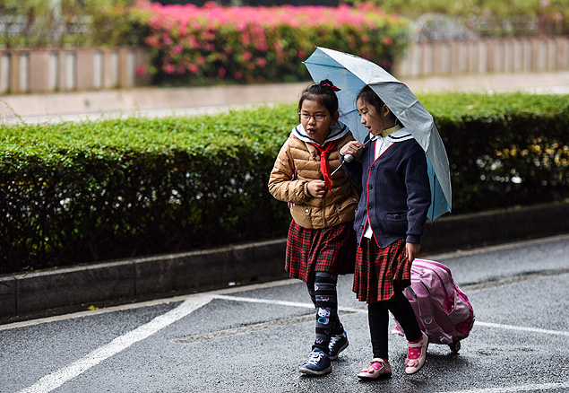 (150112) -- SHENZHEN, Jan. 12, 2015 (Xinhua) -- Children walk in the rain in Shenzhen, south China's Guangdong Province, Jan. 12, 2015. Cold air began to affect most regions in Guangdong from Jan. 12, according to the Guangdong Weather Station. (Xinhua/Mao Siqian) (rpf)