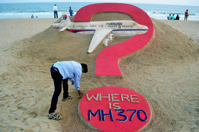 TOPSHOTS This photo taken on March 7, 2015 shows Indian sand artist Sudarsan Pattnaik creating a sand sculpture of the missing Malaysian airliner MH370 on Puri beach in eastern Odisha state. Malaysia's prime minister said March 8 his nation remains committed to the so-far fruitless hunt for flight MH370 exactly one year after it went missing, and is hopeful the plane will be found. AFP PHOTO / J.K. Jagdev ORG XMIT: JAG001