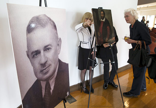 """A photograph of German Holocaust victim Dr. August Liebmann Mayer, stands next to the 17th century painting """"Portrait of a Man"""" which belonged to Dr. Mayer at a ceremony at the Jewish Heritage Museum in New York officially returning the painting to Mayer's heir, May 5, 2015. The 17th century painting taken by Nazis from a prominent German Jewish art historian has been returned to the owner's daughter, New York state officials said on Tuesday. The painting, called """"Portrait of a Man,"""" was recovered in part by the New York Department of Financial Services' Holocaust Claims Processing Office, which has helped to return $171 million in assets to relatives of holocaust victims. REUTERS/Mike Segar ORG XMIT: NYK305"""