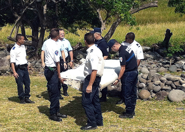 Police and gendarmes carry a piece of debris from an unidentified aircraft found in the coastal area of Saint-Andre de la Reunion, in the east of the French Indian Ocean island of La Reunion, on July 29, 2015. The two-metre-long debris, which appears to be a piece of a wing, was found by employees of an association cleaning the area and handed over to the air transport brigade of the French gendarmerie (BGTA), who have opened an investigation. An air safety expert did not exclude it could be a part of the Malaysia Airlines flight MH370, which went missing in the Indian Ocean on March 8, 2014. AFP PHOTO / YANNICK PITON ORG XMIT: REU002