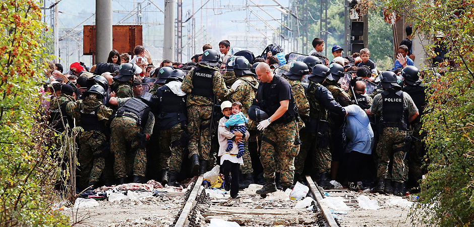 Macedonian police try to block the migrants entering Macedonia from Greece, on the border line between the two countries, near the southern Macedonia's town of Gevgelija, on Saturday, Aug. 22, 2015. About 39,000 people, mostly Syrian migrants, have been registered as passing through Macedonia in the past month, twice as many as the month before. They previously encountered little resistance at the border, but the recent influx has overwhelmed Macedonian authorities who this week declared a state of emergency and stopped many from crossing. (AP Photo/Vlatko Perkovski) ORG XMIT: XBG114