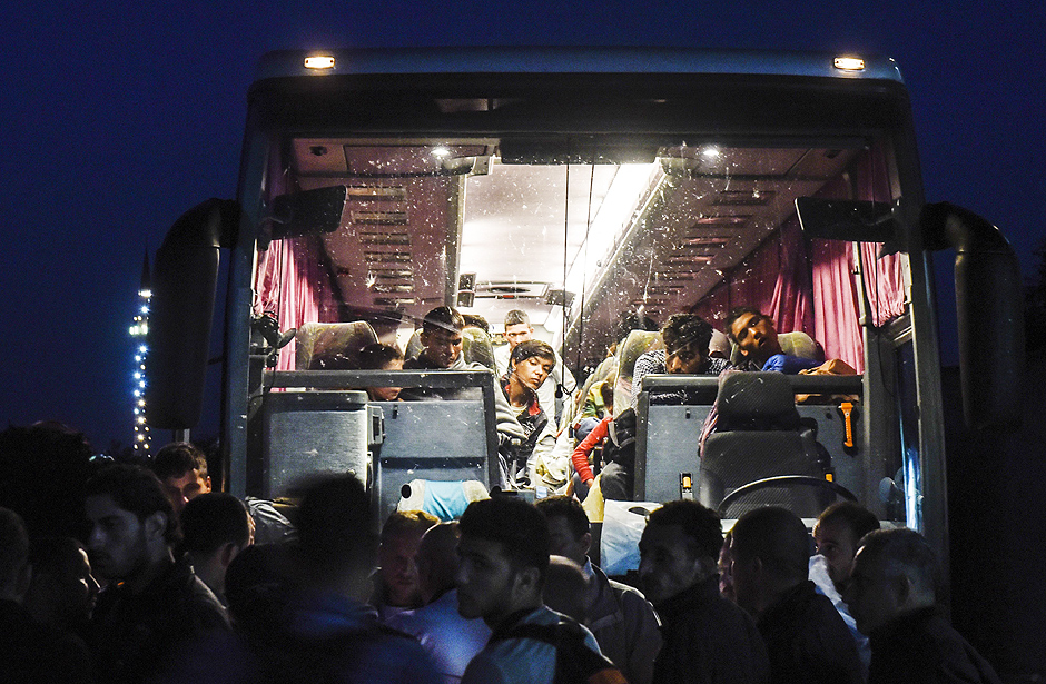 TOPSHOTS Migrants board a bus to Belgrade early in the morning in Presevo on August 24, 2015. Faced with what the bloc has called its worst refugee crisis since World War II, German Chancellor Angela Merkel and French President Francois Hollande will hold talks in Berlin on Monday in a bid to give a fresh impetus to the EU's response in dealing with the situation. AFP PHOTO/ARMEND NIMANI ORG XMIT: NIM11