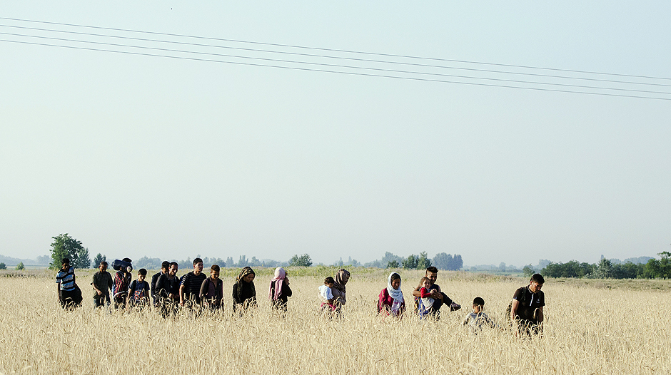 TOPSHOTS A migrant group walks onto the wheatland as they arrive at the Hungarian side of the joint Serbian border at Asotthalom village, southern Hungary, on July 7, 2015. Hungary's parliament on July 6, 2015, overwhelmingly approved the construction of a controversial fence on the border with Serbia to keep out migrants, under new legislation that also tightens asylum application rules. Over the last two years, Hungary has been one of the main routes for people hoping to cross into Austria and Germany, most coming from Afghanistan, Iraq, Syria and Kosovo. AFP PHOTO / CSABA SEGESVARI ORG XMIT: ATT8880