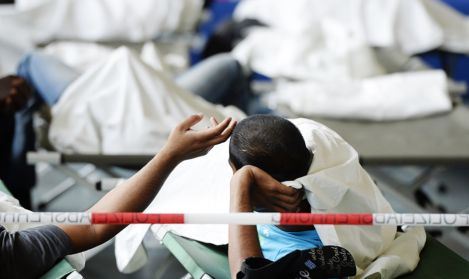 Children play as refugees wait to be processed at the first registration point of the German Federal Police in Rosenheim, southern Germany, on July 29, 2015. Hundreds of refugees arrive daily in the border region of Germany. The country, struggling with a huge influx of refugees, has been gripped by a spate of anti-foreigners rallies, violence and arson attacks against refugee homes or would-be shelters. AFP PHOTO / CHRISTOF STACHE ORG XMIT: CST007