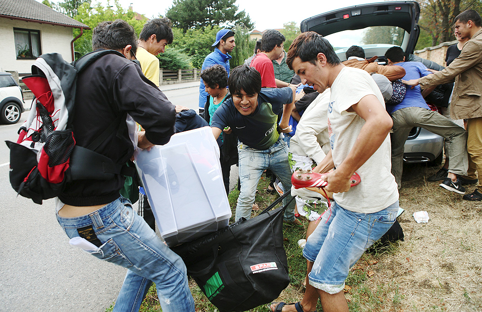 "Refugees struggle for goods delivered by private people outside the asylum processing centre in Traiskirchen, Austria, August 17, 2015. Austria's treatment of asylum seekers at the centre near Vienna is ""scandalous"", Amnesty International said on Friday, accusing the country of neglecting homeless and hungry migrants who are flocking in record numbers to western Europe. REUTERS/Heinz-Peter Bader TPX IMAGES OF THE DAY ORG XMIT: HPB01"