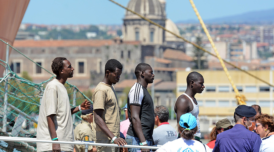 """Migrants wait in line as they disembark from the Norwegian military ship Siem Pilot in the Italian port of Catina, on August 17, 2015. At least 49 migrants died in the hold of a boat off Italy on August 15, as the EU struggled to cope with """"the worst refugee crisis since World War II"""", with thousands making dangerous crossings to reach Italy and Greece. AFP PHOTO / GIOVANNI ISOLINO ORG XMIT: -"""