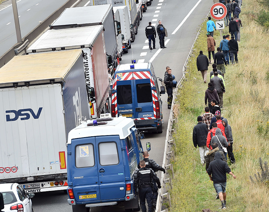 "TOPSHOTS French riot police stand on the side of the road to prevent migrants from approaching lorries on the road leading to the ferry port in Calais, northern France, on August 5, 2015. Britain and France were to announce a new ""command and control centre"" on August 20 for tackling smuggling gangs in Calais, where thousands of migrants desperate to cross the Channel are living in slum-like conditions. AFP** PHOTO / PHILIPPE HUGUEN ORG XMIT: 2216"