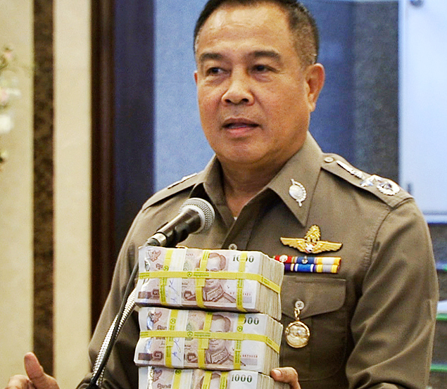 In this image taken from video, National police chief Somyot Poompanmoung holds a cash reward at a press conference in Bangkok, Thailand, Monday, Aug. 31, 2015. Thai police have awarded themselves a 3 million baht ($84,000) reward offered to the public for tips leading to the arrest of suspects in Bangkok's deadly bombing after a man was arrested over the weekend in an apartment where police found bomb-making equipment. (AP Photo/AP Video) ORG XMIT: BKK201