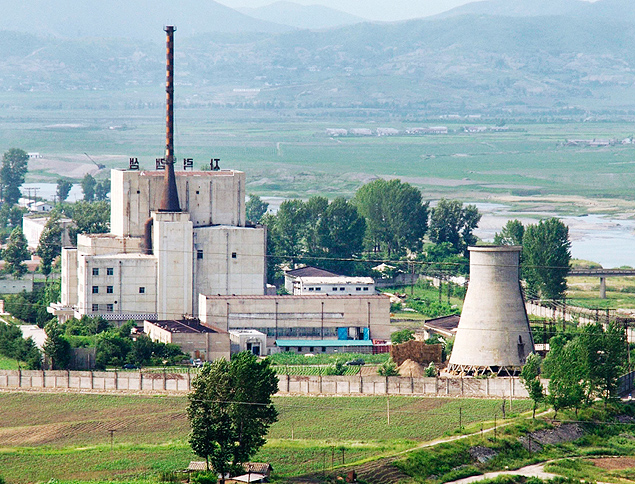 Vista de usina nuclear norte-coreana, antes de demolir a torre de resfriamento (Dir,), em Yongbyon (Coreia do Norte). *** ORG XMIT: TOK002 A North Korean nuclear plant is seen before demolishing a cooling tower (R) in Yongbyon, in this photo taken June 27, 2008 and released by Kyodo. North Korea is to restart the mothballed Yongbyon nuclear reactor that has been closed since 2007 in a move that could produce more plutonium for nuclear weapons as well as for domestic electricity production, its KCNA news agency said on April 2, 2013. As well as restarting the 5MW reactor at Yongbyon, the North's only known source of plutonium for its nuclear weapons programme, KCNA said a uranium enrichment plant would also be put back into operation, a move that could give it a second path to the bomb. Picture taken June 27, 2008. Mandatory Credit. REUTERS/Kyodo (NORTH KOREA - Tags: ENERGY POLITICS TPX IMAGES OF THE DAY) FOR EDITORIAL USE ONLY. NOT FOR SALE FOR MARKETING OR ADVERTISING CAMPAIGNS. MANDATORY CREDIT. JAPAN OUT. NO COMMERCIAL OR EDITORIAL SALES IN JAPAN. ATTENTION EDITORS - THIS IMAGE WAS PROVIDED BY A THIRD PARTY. THIS PICTURE IS DISTRIBUTED EXACTLY AS RECEIVED BY REUTERS, AS A SERVICE TO CLIENTS. YES