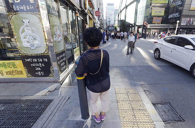 """In this Sept. 17, 2015 photo, an elderly woman stands at a small, bustling plaza in front of the Piccadilly theater in Seoul, South Korea. It's a place where elderly prostitutes openly solicit customers for sex in nearby motels. They are dubbed """"Bacchus ladies"""" after the popular energy drink that they have traditionally sold.(AP Photo/Ahn Young-joon) ORG XMIT: XSEL101"""