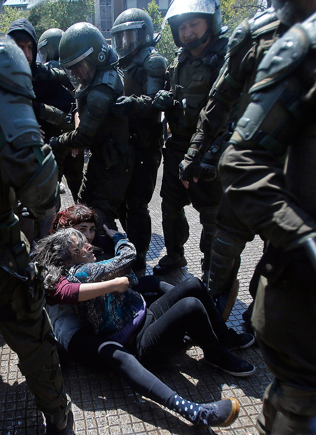 Protesters embrace on the ground as they're detained by police after a student protest ended in clashes in Santiago, Chile, Thursday, Oct. 15, 2015. Demonstrators marched to complain about delays in an education overhaul and ask President Michelle Bachelet to fulfill her campaign promise of free education. (AP Photo/Luis Hidalgo) ORG XMIT: XLHP107