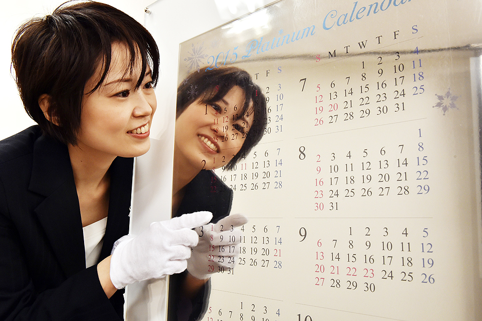 An employee of Japanese jeweler Tanaka Kikinzoku Jewelry displays a pure platinum made calendar for 2015 at the company's Ginza shop in Tokyo on December 3, 2014. The calendar measuring 77cm x 50cm and weighing 10 kilograms is priced at 100 million yen (840,000 USD). AFP PHOTO / Yoshikazu TSUNO ORG XMIT: TOK6076