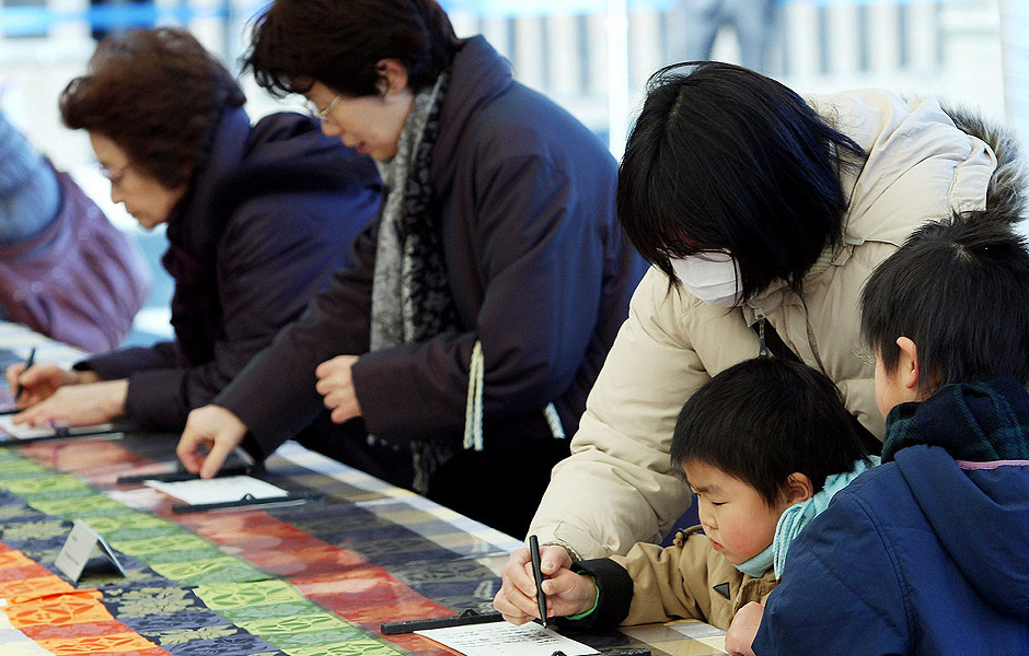 ORG XMIT: TY047 People write their names on notes to hope quick recovery of Emperor Akihito at the Imperial Palace in Tokyo on February 18, 2012. Emperor Akihito went into surgery for a heart bypass operation. AFP PHOTO/JIJI PRESS