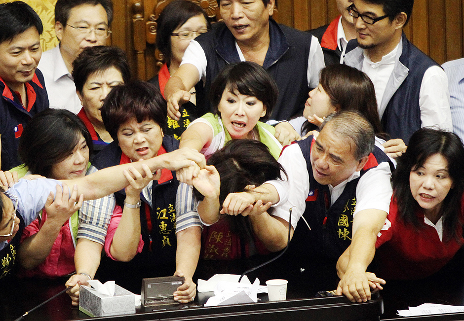 TOPSHOTS Legislators from Taiwan's ruling Kuomintang party and opposition try to seize the parliament's podium on June 25, 2013. Fighting broke out in Taiwan's parliament as legislators scuffled and threw coffee during a debate on whether a controversial capital gains tax on share trading should be revised less than a year after it was brought in. TAIWAN OUT AFP PHOTO ORG XMIT: CMC088