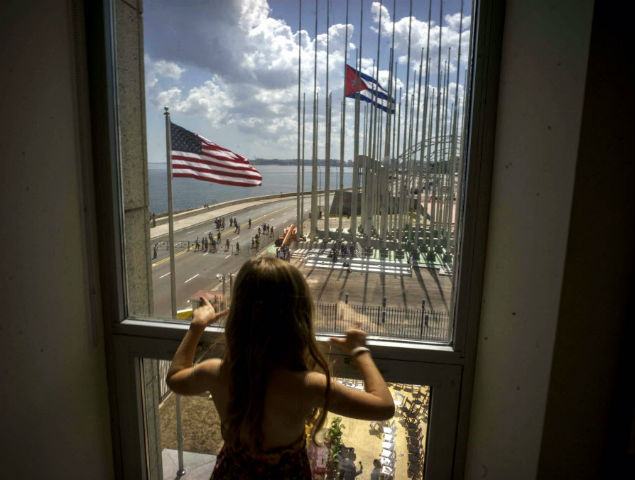 Aug. 14, 2015 file photo, a girl looks out the window at the area of the flag raising ceremony, from inside the newly opened U.S. embassy in Havana, Cuba. In the year since Presidents Raul Castro and Barack Obama announced a rapprochement between bitter Cold War enemies, Cuba has been transformed, for better or worse. (AP Photo/Ramon Espinosa, File) ORG XMIT: CUB301