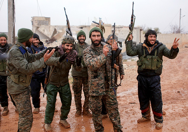 Syrian government soldiers celebrate after taking control of the village of Ratian, north of the embattled city of Aleppo, from rebel fighters on February 6, 2016. Thousands of Syrians fled towards Turkey as regime troops pressed a major Russian-backed offensive around Aleppo, that threatens a fresh humanitarian disaster. / AFP / GEORGE OURFALIAN