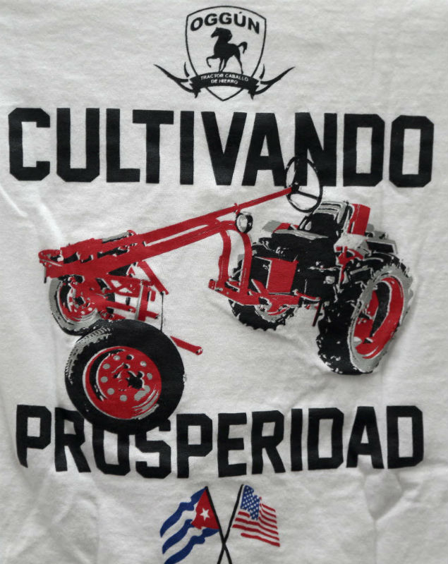 """In this Feb. 12, 2016 photo, a logo on a T-shirt which reads in Spanish """"Cultivating prosperity"""" hangs on display at the office of tractor maker Saul Berenthal in Raleigh, N.C. The Obama administration has approved the first U.S. factory in Cuba in more than half a century, allowing a pair of former software engineers to build a plant assembling as many as 1,000 small tractors a year. The partners were notified by Treasury Department officials last week that it was legal for them to open their Oggun tractor assembly plant in a special economic zone created by the Cuban government to draw foreign investment. (AP Photo/Gerry Broome) ORG XMIT: NCGB303"""