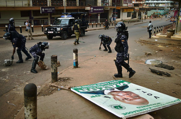 Ugandan police officers remove barricades set up by opposition supporters protesting against President Yoweri Museveni in Kampala after he won the presidential election for a fifth term on February 20, 2016. Uganda's President Yoweri Museveni extended his three-decade rule, after winning a fifth term in polls rejected as fraudulent by the opposition leader under house arrest. The veteran 71-year-old won 60 percent of the vote in the sometimes chaotic elections, far ahead of the 35 percent garnered by detained opposition chief Kizza Besigye, whose house was surrounded by dozens of armed police in riot gear. / AFP / CARL DE SOUZA ORG XMIT: 2102