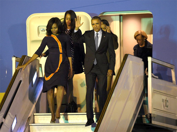 US President Barack Obama and First Lady Michelle Obama arrive with their daughters Sasha and Malia at Ministro Pistarini International Airport in Ezeiza, Argentina. Obama will meet Argentine counterpart Mauricio Macri before laying a wreath at a monument at Buenos Aires Metropolitan Cathedral, meeting young businesspeople and attending a dinner in his honor. / AFP PHOTO / JUAN MABROMATA