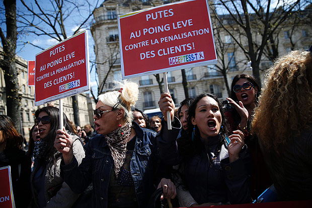 "A protester (R) holds a sign reading ""Prostitutes with fists raised against the penalization of clients!"" during a demonstration by sex workers and supporters near the French National Assembly in Paris on April 6, 2016, as French lawmakers take part in a final debate on a bill that would make it illegal to pay for sex. French lawmakers were poised on April 6 to pass a controversial law that makes it illegal to pay for sex and imposes fines of up to 3,500 euros ($3,970) on prostitutes' clients. / AFP PHOTO / THOMAS SAMSON ORG XMIT: 1858"