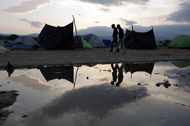 Migrant men are reflected in a pond as they walk among tents, at the makeshift camp at the northern Greek border point of Idomeni, Greece, Monday, April 11, 2016. More than 12,000 people have been stuck her for more than a month amid hopes that the border would reopen. (AP Photo/Amel Emric) ORG XMIT: XAE114