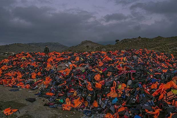 A huge pile of discarded life vests, inner tubes and deflated rubber dinghies, the basic equipment that thousands of refugees have used to cross the Aegean Sea from Turkey, at dusk on the Greek island of Lesbos (Mauricio Lima, The New York Times - November 7, 2015).