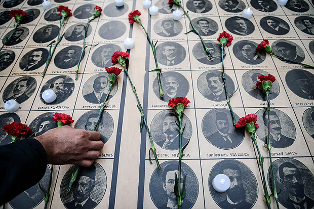 People lay red carnations on pictures of Armenian intellectuals, detained and deported in 1915, during a rally on April 24, 2016 to commemorate the 101th anniversary of the 1915 mass killing of Armenians in the Ottoman Empire at Istiklal avenue in Istanbul. Armenians say up to 1.5 million people were killed during World War I as the Ottoman Empire was falling apart, a claim supported by many other countries. Turkey fiercely rejects the genocide label, arguing that 300,000 to 500,000 Armenians and at least as many Turks died in civil strife when Armenians rose up against their Ottoman rulers and sided with invading Russian troops. / AFP PHOTO / OZAN KOSE ORG XMIT: 6228