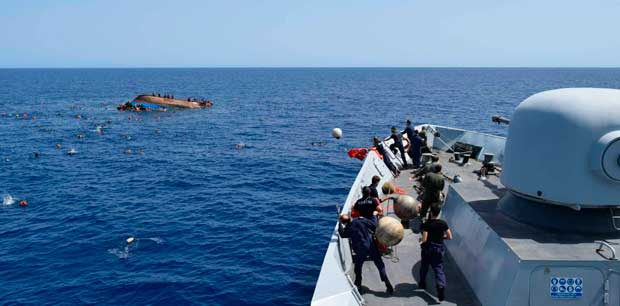 """TOPSHOT - This handout picture released on May 25, 2016 by the Italian Navy (Marina Militare) shows the shipwreck of an overcrowded boat of migrants off the Libyan coast today. At least seven migrants have drowned after the heavily overcrowded boat they were sailing on overturned, the Italian navy said. The navy said 500 people had been pulled to safety and seven bodies recovered, but rescue operations were continuing and the death toll could rise. The navy's Bettica patrol boat spotted """"a boat in precarious conditions off the coast of Libya with numerous migrants aboard,"""" it said in a statement. / AFP PHOTO / MARINA MILITARE AND AFP PHOTO / STR / RESTRICTED TO EDITORIAL USE - MANDATORY CREDIT """"AFP PHOTO / MARINA MILITARE"""" - NO MARKETING NO ADVERTISING CAMPAIGNS - DISTRIBUTED AS A SERVICE TO CLIENTS"""