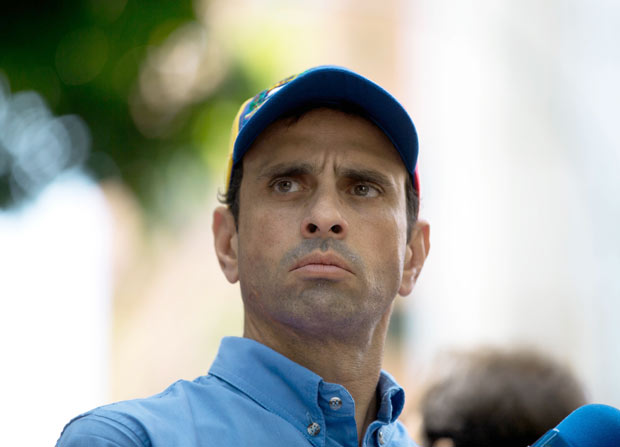 Opposition leader Henrique Capriles looks out on a crowd during a protest outside the court offices of the Chacao municipality, in Caracas, Venezuela, Wednesday, May 25, 2016. Opposition members held a demonstration to demand authorities hold a recall referendum on cutting short Nicolas Maduro's presidency. (AP Photo/Fernando Llano)
