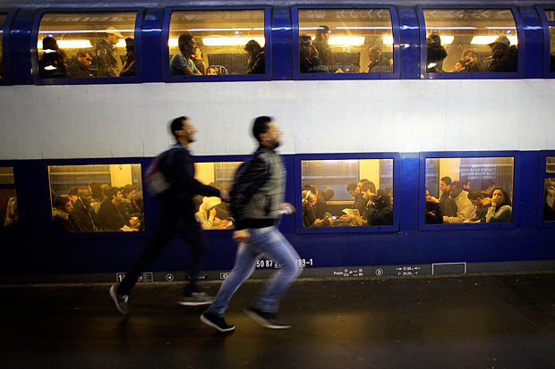 Two men run to catch one of the few trains running after a strike starts at the Gare Saint Lazare train station, in Paris, Wednesday, June 1, 2016. Workers at the SNCF national rail authority, whose train service will be crucial to Euro 2016 spectators, are on an open-ended strike to protest their working conditions and a controversial government labor reform. (AP Photo/Markus Schreiber) ORG XMIT: MSC103