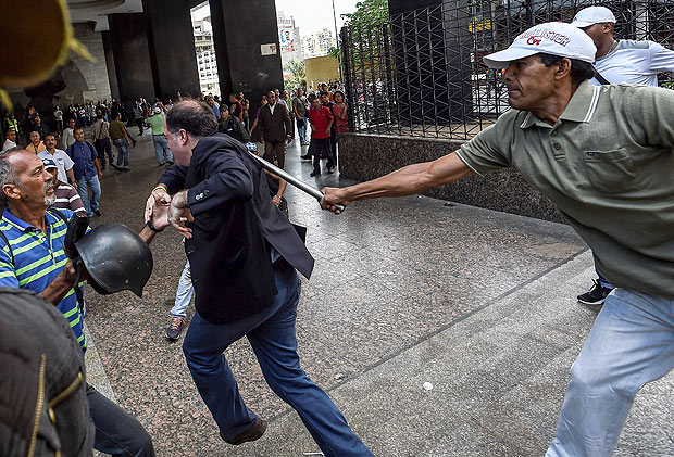 Supporters of Venezuelan president Nicolas Maduro hit opposition deputy Julio Borges(C), during a demonstration in front of the National Electoral Council in Caracas on June 9, 2016. / AFP PHOTO / JUAN BARRETO / ALTERNATIVE CROP