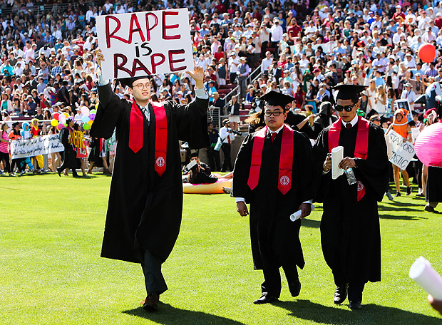 Stanford student Paul Harrison (C) carries a sign in a show of solidarity for a Stanford rape victim during graduation ceremonies at Stanford University, in Palo Alto, California, on June 12, 2016. Stanford students are protesting the university's handling of rape cases alledging that the campus keeps secret the names of students found to be responsible for sexual assault and misconduct. / AFP PHOTO / GABRIELLE LURIE