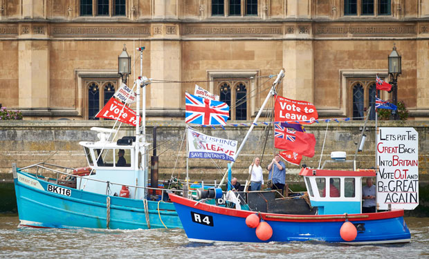 "Boatsd decorated with flags and banners from the 'Fishing for Leave' group that are campaigning for a 'leave' vote in the EU referendum sail by the British Houses of Parliament as part of a ""Brexit flotilla' on the river Thames in London on June 15, 2016. A Brexit flotilla of fishing boats sailed up the River Thames into London today with foghorns sounding, in a protest against EU fishing quotas by the campaign for Britain to leave the European Union. / AFP PHOTO / NIKLAS HALLE'N"
