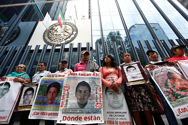 Relatives hold posters with images of some of the 43 missing students of Ayotzinapa College Raul Isidro Burgos as they protest to demand justice for the missing students, during a march to mark the 21-month anniversary of their disappearance, outside the Attorney General's Office (PGR) headquarters in Mexico City, Mexico, June 26, 2016. REUTERS/Edgard Garrido ORG XMIT: EGC10