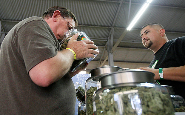 A medical marijuana user smells a jar of marijuana at the medical marijuana farmers market at the California Heritage Market in Los Angeles, California July 11, 2014. REUTERS/David McNew/File Photo ORG XMIT: TOR604