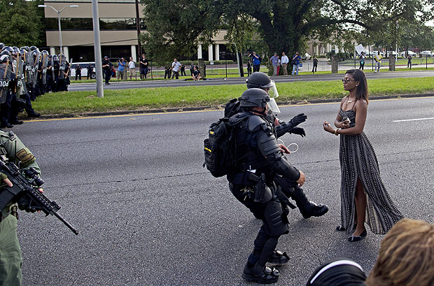 A protester is grabbed by police officers in riot gear after she refused to leave the motor way in front of the the Baton Rouge Police Department Headquarters in Baton Rouge, La., Saturday, July 9, 2016. Several hundred protesters, including members of the New Black Panther party, blocked the roadway causing police to close the road and move the crowd with riot police. Several protesters were arrested.(AP Photo/Max Becherer) ORG XMIT: LAMB108