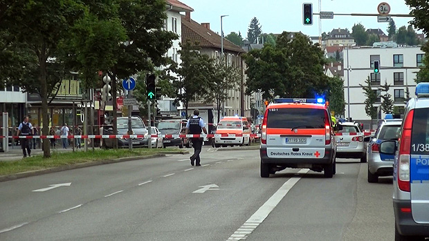 GERMANY OUT - In this grab taken from video, police officers secure the area after a machete attack in Reutilingen, Germany, Sunday, July 24, 2016. A Syrian man killed a woman with a machete and wounded two others Sunday outside a bus station in the southwestern German city of Reutlingen before being arrested. Police said there were no indications pointing to terrorism. (NONSTOP NEWS via AP) ORG XMIT: LON838