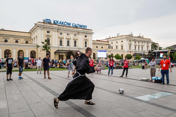 Young people and a monk play soccer in front of the main railway station in Krakow, Poland, on July 25, 2016, one day ahead of the official opening of the world's youth days, with the participation of Pope Francis. / AFP PHOTO / WOJTEK RADWANSKI ORG XMIT: WRAD2509
