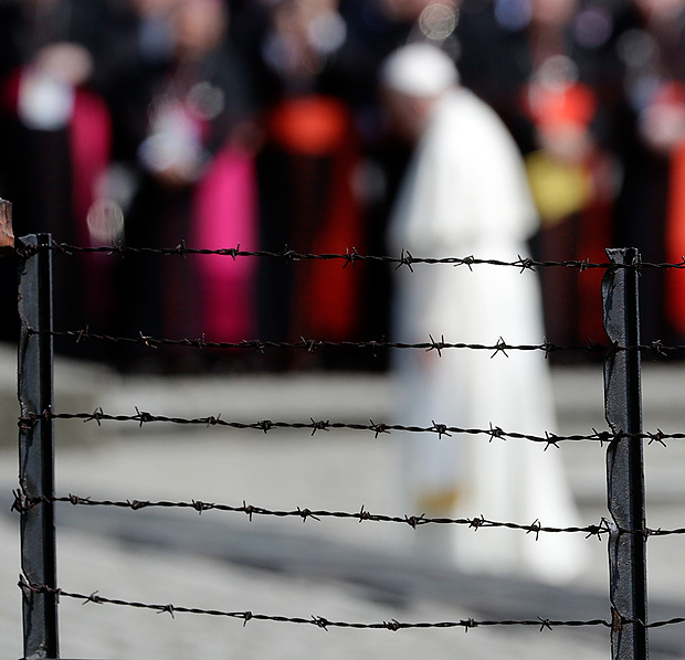Pope Francis, background, is framed by a barbed wire as he prays in front of the Memorial at the former Nazi Death Camp Auschwitz-Birkenau, in Oswiecim, Poland, Friday, July 29, 2016. Pope Francis paid a somber visit to the Nazi German death camp of Auschwitz-Birkenau Friday, becoming the third consecutive pontiff to make the pilgrimage to the place where Adolf Hitler's forces killed more than 1 million people, most of them Jews. (AP Photo/Gregorio Borgia) ORG XMIT: GB130