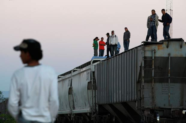 "Central American migrants stand atop wagons while waiting for the freight train ""La Bestia"", or the Beast, to travel to north Mexico to reach and cross the U.S. border, in Arriaga in the state of Chiapas January 10, 2012. REUTERS/Jorge Luis Plata/File Photo ORG XMIT: CDG07"