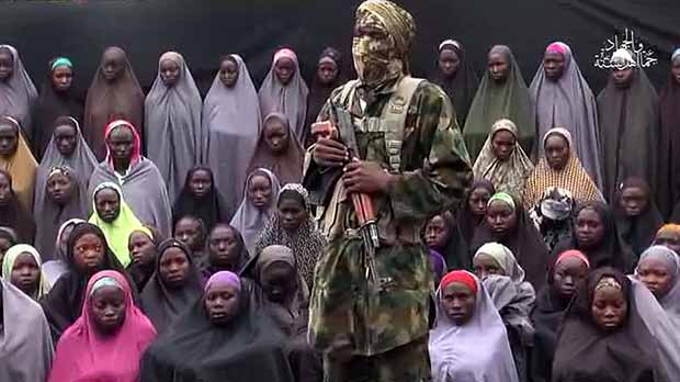 "TOPSHOT - This video grab image created on August 14, 2016 taken from a video released on youtube purportedly by Islamist group Boko Haram showing what is claimed to be one of the groups fighters at an undisclosed location standing in front of girls allegedly kidnapped from Chibok in April 2014. Boko Haram on August 14, 2016 released a video of the girls allegedly kidnapped from Chibok in April 2014, showing some who are still alive and claiming others died in air strikes. The video is the latest release from embattled Boko Haram leader Abubakar Shekau, who earlier this month denied claims that he had been replaced as the leader of the jihadist group. / AFP PHOTO / HO / RESTRICTED TO EDITORIAL USE - MANDATORY CREDIT ""AFP PHOTO / BOKO HARAM"" - NO MARKETING NO ADVERTISING CAMPAIGNS - DISTRIBUTED AS A SERVICE TO CLIENTS"