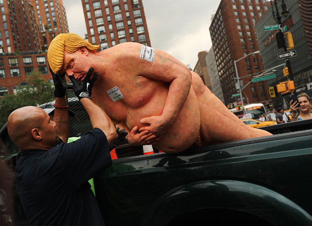 """NEW YORK, NY - AUGUST 18: Park authorities haul away a statue of a naked GOP presidential candidate Donald Trump that appeared in Union Square Park this morning on August 18, 2016 in New York City. The illegally placed statue drew hundreds of curious onlookers, who took selfie picture with the statue, which was signed """"Ginger."""" A published report attributed the work to the anarchist collective INDECLINE, which titled the project """"The Emperor Has No B--s."""" Spencer Platt/Getty Images/AFP == FOR NEWSPAPERS, INTERNET, TELCOS & TELEVISION USE ONLY =="""